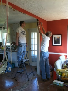 men doing man stuff, like cutting out wallboard